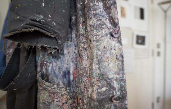 Photo of paint covered coat in artist studio