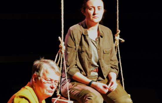 Photo of two actors, one sitting on a swing