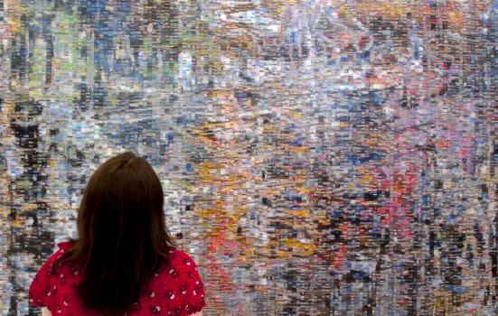 Photo of woman looking at wall of tiny images