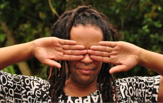A Black person covering their each eye with their hands, palms facing towards the camera