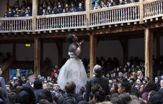 Photo of young people watching woman on stage
