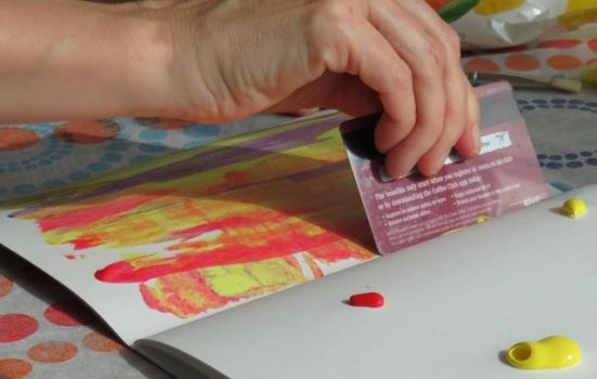 Photo of person scraping paint in exercise book with bank card