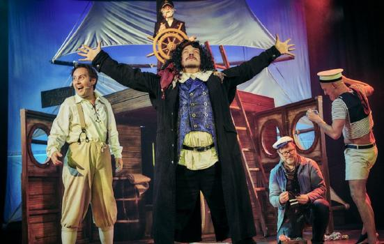A pirate on stage performing Treasure Island in front of a ship prop and his crew