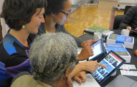 Photo of three women looking at tablets