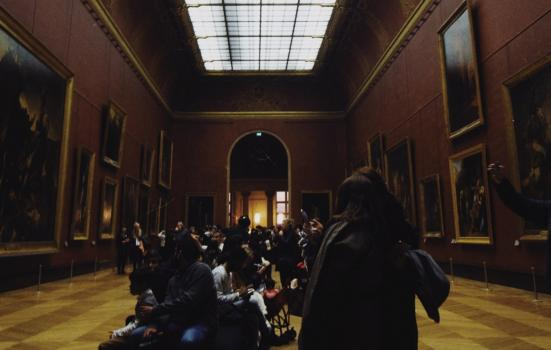 A group of people gathered in the centre of a gallery