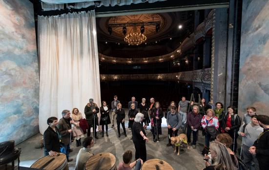 Describer Roz Chalmers on stage with participants of the touch tour for Rosencrantz & Guildenstern are Dead, Old Vic.