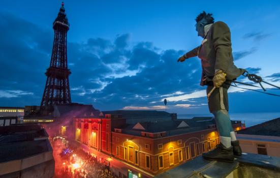 Photo of man standing on top of building with crowd and Blackpool Tower