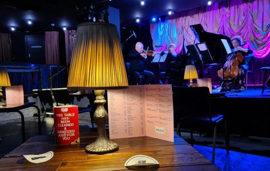 A table in the foreground with a lamp, menu and 'I have been sanitised' marker with a band on stage in the background