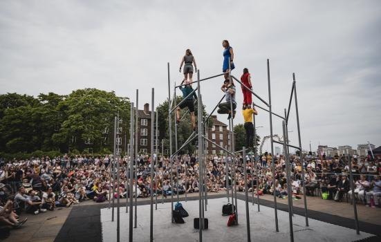 A photo of people standing on a tall metal structure on a stage