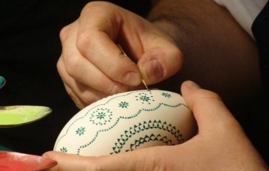 A close up photo of hands painting an Easter egg