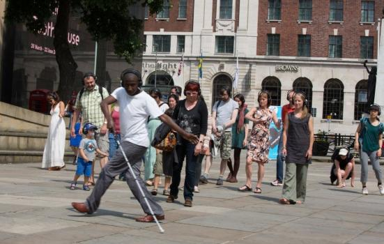 Photo of man dancing with a white cane followed by audience
