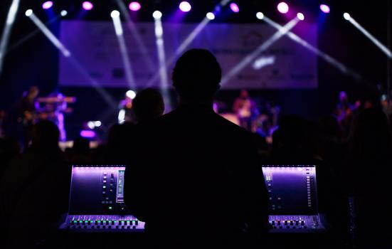 dark silhouette of a sound operator (taken from behind) in a theatre or music show with lights onto the stage