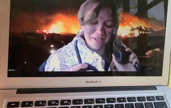 image of a woman on a MacBook Air screen with an explosion behind her