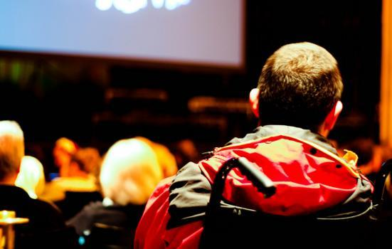 Photo of a person in a wheelchair at the theatre