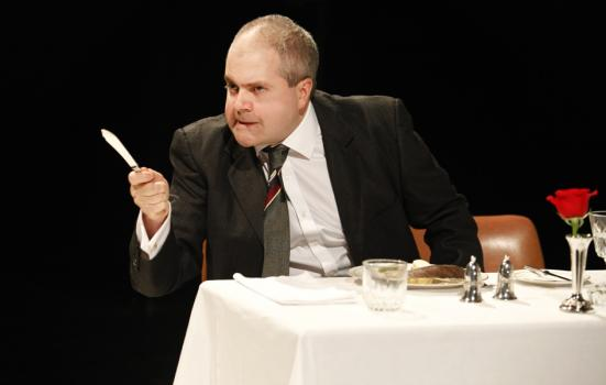 Production shot - man at table holding a knife