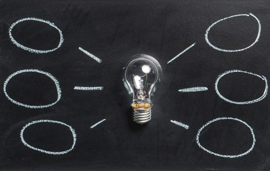 A light bulb in front a a blackboard with thought bubble drawings