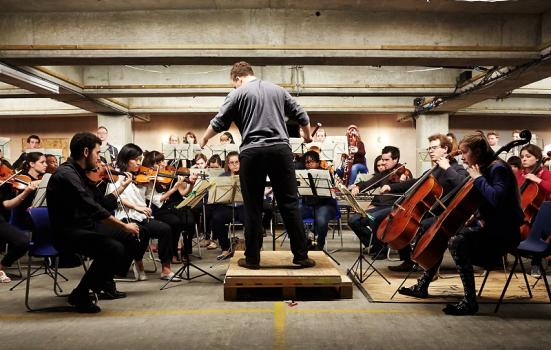 Photo of an orchestra playing in a car park