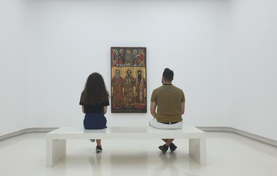 man and woman sitting on a bench looking at a painting in a gallery - view from behind the couple