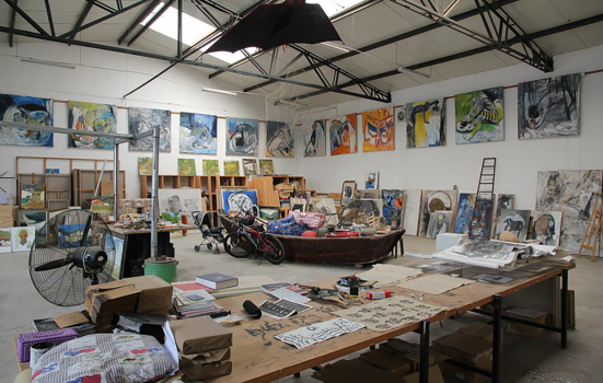 an artist's studio with paintings all around