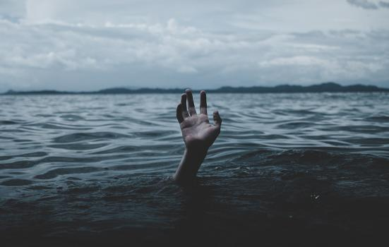 Photo of a lone hand rising up out of the water in a lake