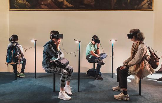 four people sitting in a gallery wearing virtual reality headsets