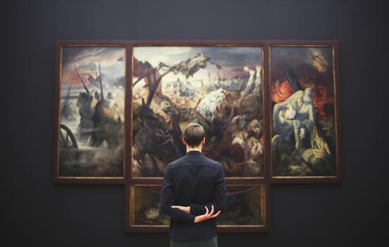 a young man, back to us, viewing picture in a gallery