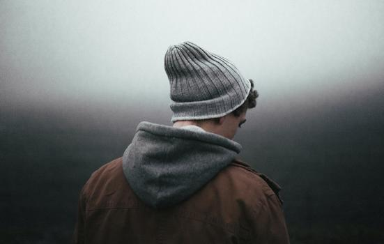 young man with woolly hat and hooded jacket facing downward and away from camera into a foggy background