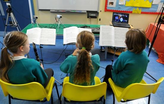 Photo of children having music lesson via internet