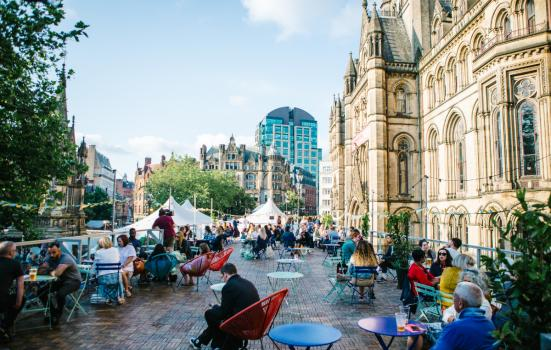 People sitting in tables outside in Manchester