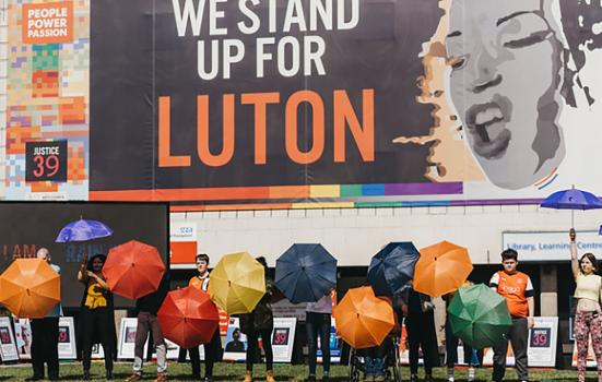Revoluton picture of people carrying cooured umbrellas in front of building with mural 'We stand up for Luton'