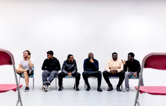 Young men sitting in a row on chairs laughing