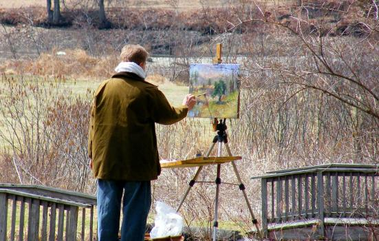 Photo of a man painting outside