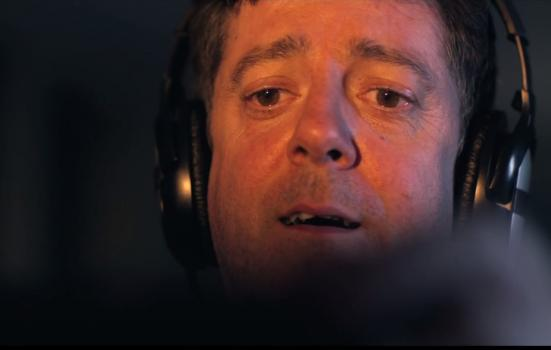 Still from the film of a man wearing headphones