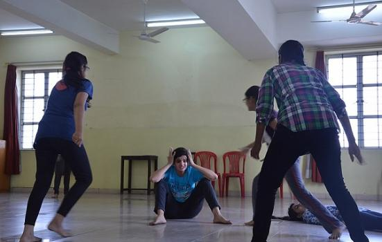 A theatre workshop in which students rush at a young person seated on the ground