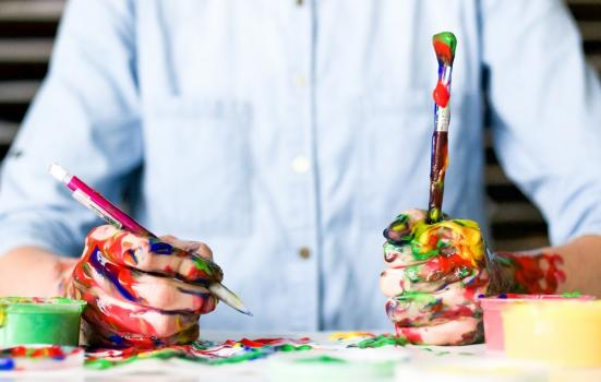 Photo of man with paintbrushes and pen