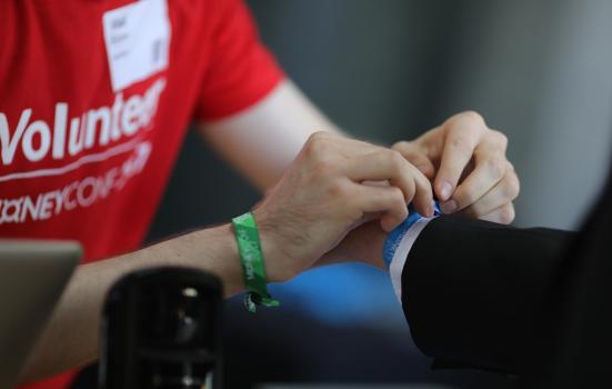 Volunteer attaching a wrist band to another person