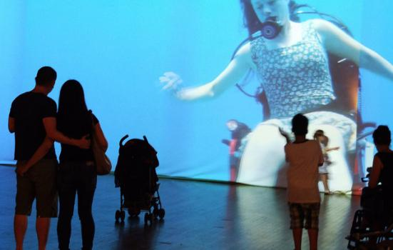 Photo of audience watching a film of a disabled dancer underwater