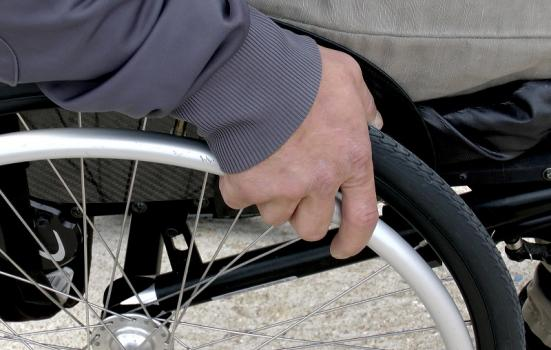 Photo of hand on a wheelchair wheel