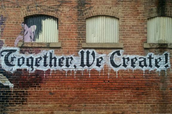 "Photo of a wall graffitied with the words ""Together We Create!"""