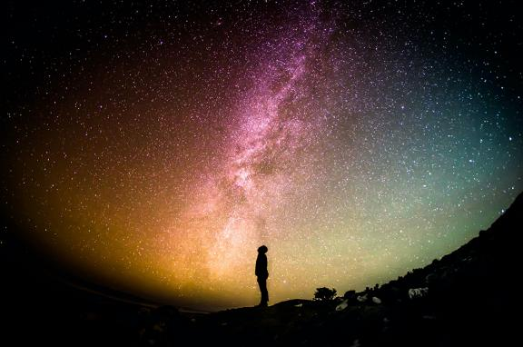 silhouette of a person looking up at a coloured starry sky