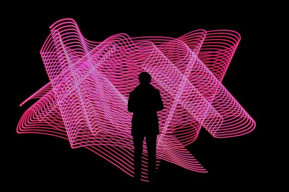 Silhouette of a person in front of a neon pink light display
