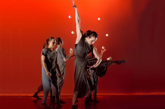 Photo of four performers, two juggling in the background, and the lead dancing in the foreground