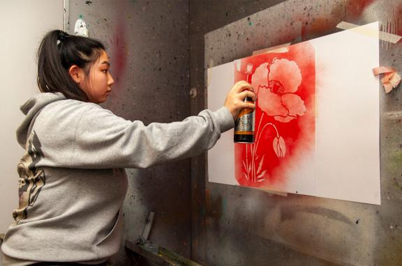 A girl spray painting a poppy onto a wall using a stencil