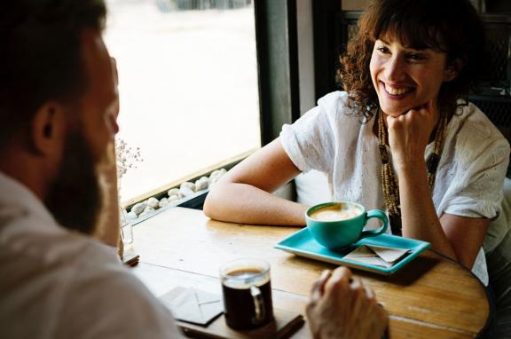 Photo of a man and women chatting over coffee