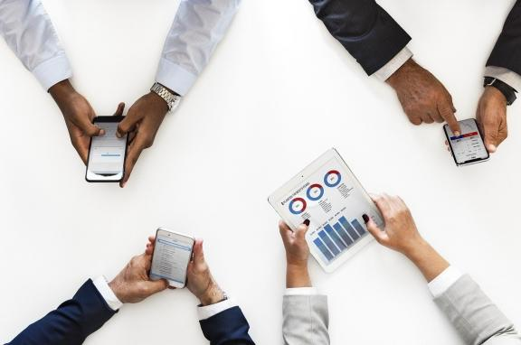 A picture of four people's hands holding mobile devices