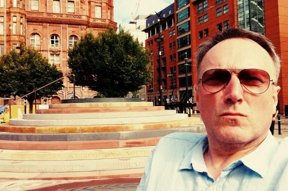 photo of Andrew Miller beside Jeremy Miller's Peterloo Memorial in Manchester