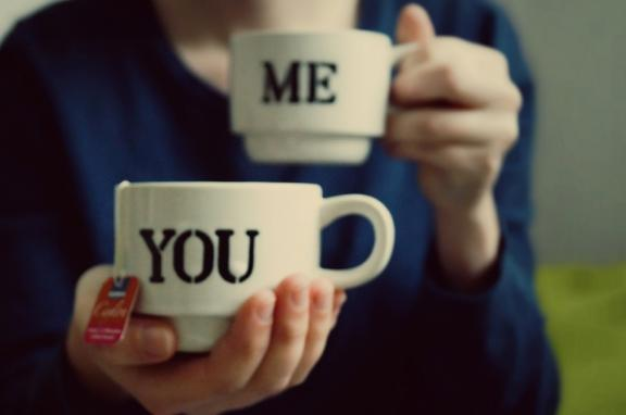 Photo of person offering coffee cup