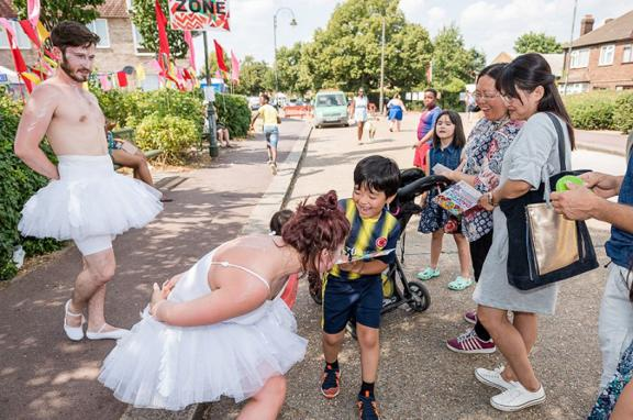 Photo of a man and woman in ballet dress addressing a family on the street