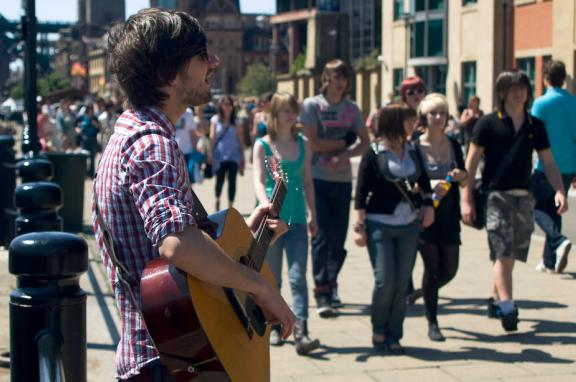 Photo of man playing guitar on the street
