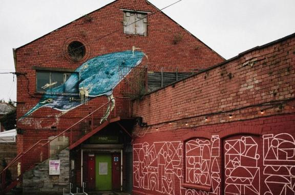 A photo of a red brick building with graffiti